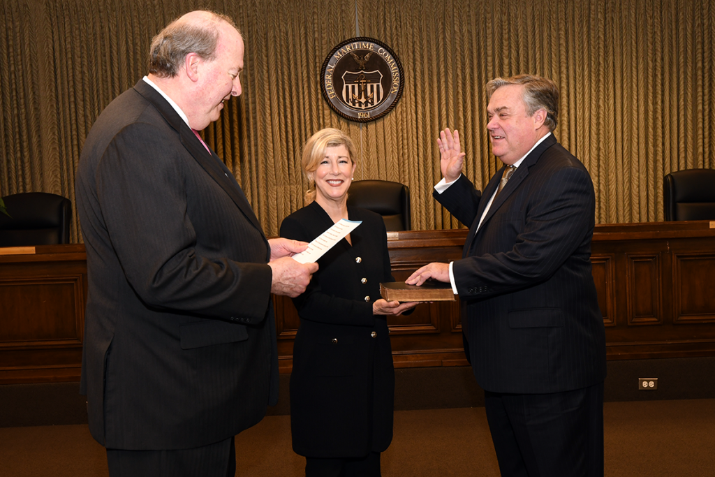 Chairman Khouri (left) administers oath of office to Commissioner Bentzel (right) who is joined by his wife, Suzanne Bentzel (center)